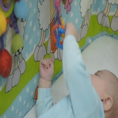 The baby is in the playpen, picks up a toy and tries to shove in your mouth Stock Footage