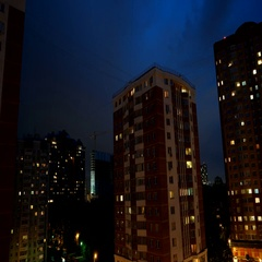 Timelapse of night sky over apartment buildings. Clouds float in the sky, light Stock Footage