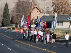 School children march in Veterans Day parade with flags DCI 4K Stock Footage