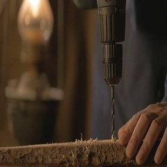 The carpenter makes a hole in the Board drill. master works in the Studio tool Stock Footage