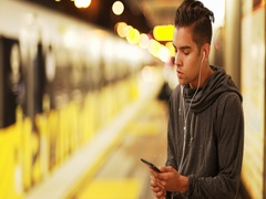Millennial Latino man using smartphone waiting for subway train at metro station Stock Footage