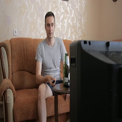 The man taking beer wanted to watch TV, but his old retro TV does not work. Stock Footage