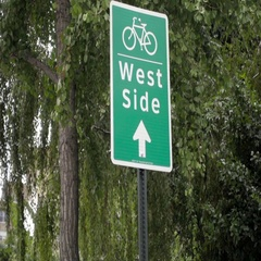 Sign for West Side with trees moving in spring in Downtown Manhattan NYC Stock Footage