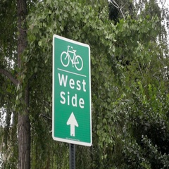 West Side sign with bicycle image in front of trees in Lower East Side NYC Stock Footage
