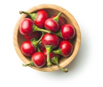 Round red chili peppers in bowl isolated on white background. Stock Photos