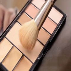 Close up of makeup brush moving over eye shadows Stock Footage