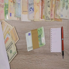 Banker counting Euros at his office table, World currencies around him Stock Footage