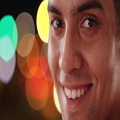 Close up portrait of Happy Latino man looking at camera on city street at night Stock Footage
