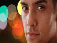 Close up portrait of Latino man looking at camera on city street at night Stock Footage