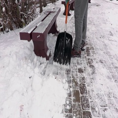 Janitor with snow shovel working on sidewalk near benches Stock Footage