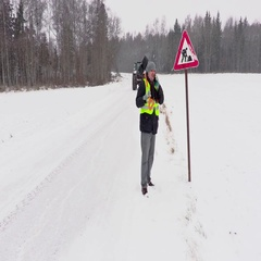 Worker with snow shovel near road sign Stock Footage