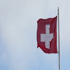 Switzerland National Flag Waving in the Wind against a Blue Sky Stock Footage
