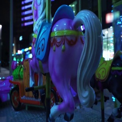 Concept - lifetime. POV of Horses on Carousel of Night City Panorama Closeup Stock Footage