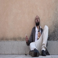Drunk man sitting on the street with bottle and cigarette Stock Footage