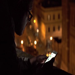 man with glasses in twilight on the terrace using his smartphone Stock Footage