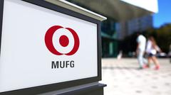 Street signage board with MUFG logo. Blurred office center and walking people Stock Illustration