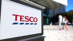 Street signage board with Tesco logo. Blurred office center and walking people Stock Illustration