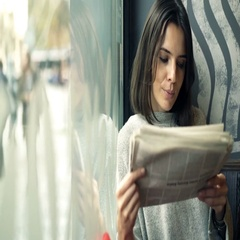 Young woman reading newspaper sitting in cafe by window, 4K Stock Footage