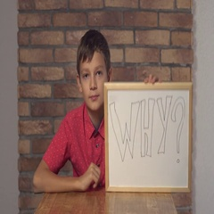 Child sitting at the desk holding flipchart with lettering why on the background Stock Footage