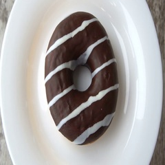 Delicious sweet donut with chocolate icing rotating on a plate. Rustic wooden Stock Footage