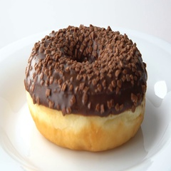 Delicious sweet donut with chocolate icing rotating on a plate. White background Stock Footage