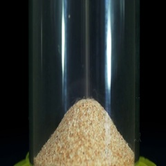 Hourglass on a Black Background, the Sand Falls Inside Stock Footage