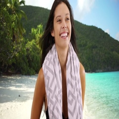 Medium shot of a young white girl standing on a Caribbean beach with a towel Stock Footage