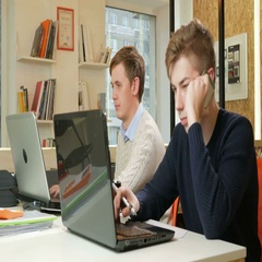 Young man working in the office of the laptops on the project. One is calling on Stock Footage