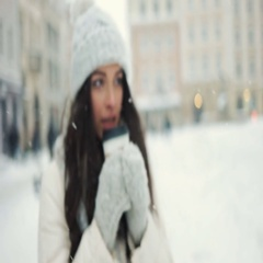 Smiling young woman in white warm clothes with and drinking coffee to take away Stock Footage