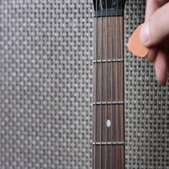 Taking plectrum from electric guitar fretboard Stock Footage