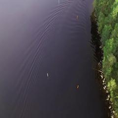 Aerial shot of a small passenger boat turning at a narrow sea lane at a Nordic Stock Footage