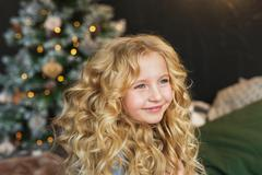 Portrait of pretty blonde little girl smiles and looks side in Christmas time Kuvituskuvat