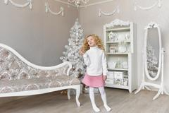 Pretty little girl stands in a light new year decoration studio Stock Photos