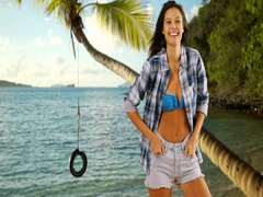 Young white girl poses near the Caribbean shore and a rope-tire swing Stock Footage