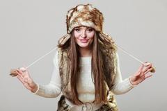 Closeup smiling young woman wearing fashionable wintertime clothes fur cap Stock Photos