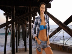 Millennial white woman stands under the pier posing for a portrait Stock Footage
