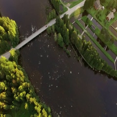 Fish farm pools by a streaming river in Finland, aerial tilt shot with lens Stock Footage