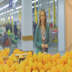 Woman selecting fresh oranges in grocery store produce department and smelling i Stock Footage