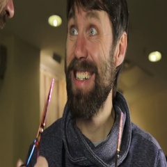 Close-up Young Handsome man trimming beard with scissors and looks in a mirror Stock Footage