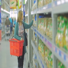 Young woman chooses food in the supermarket, Mother chooses food for their child Stock Footage