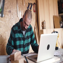 Bold carpenter with vintage moustache is using a laptop while working in the wor Stock Footage