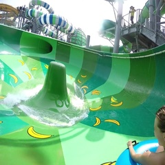 Happy man and woman riding down the water slide. People having fun in water park Stock Footage