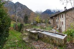 Old fountains in a village of the Italian alps Stock Photos