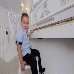 Small boy sits at the piano. boy smiling with his toothless mouth. Stock Footage