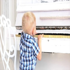 Small boy enjoys playing piano, for the first time. Stock Footage