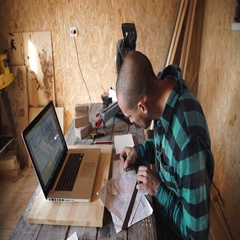 Young bold carpenter with moustache drawing in his workshop Stock Footage