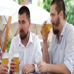 Three men in cafe drinking light beer, talking Stock Footage