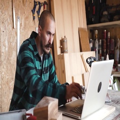 Bold with moustache young Carpenter Craftsman do drawing with laptop in his Stock Footage