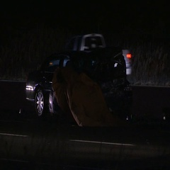 Police at scene of fatal car accident on dark highway at night Stock Footage