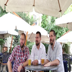 Three young men with beer watching sport match in cafe Stock Footage